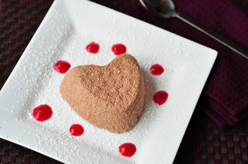 Coeur a la creme au chocolat on a white plate with raspberry coulis
