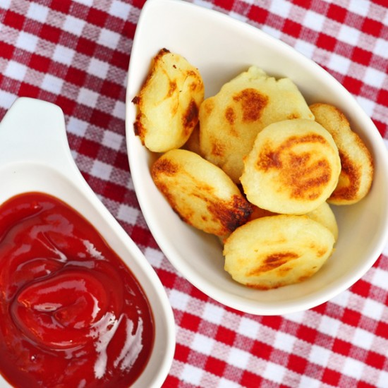 A version of Duchess potatoes in a small bowl on a checkered tablecloth with tomato ketchup