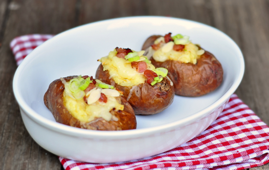Klondike Rose twice baked potatoes with bacon green onions Greek yogurt almonds and cheese in a white dish on a checkered napkin