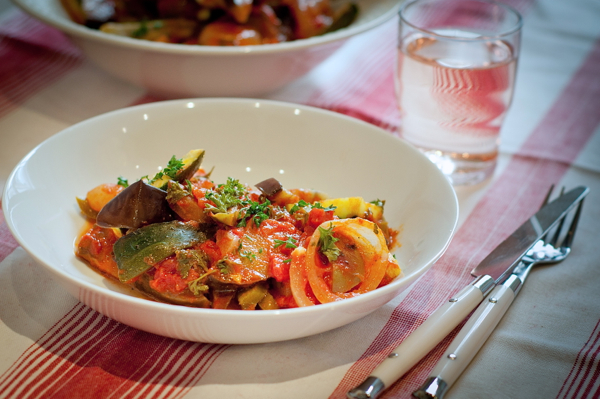 Julia Child's ratatouille recipe in a white bowl with a glass of rosé