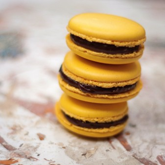 Stack of Italian meringue macarons filled with chocolate passionfruit ganache