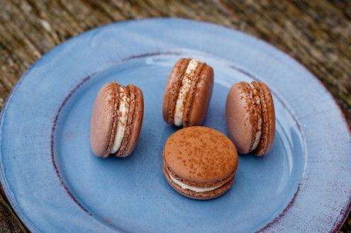 chocolate basil macaron with passion fruit cream cheese on a blue plate
