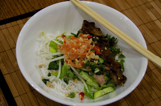 Lemongrass pork and beef skewers on vermicelli with green onion sauce and pickled carrots