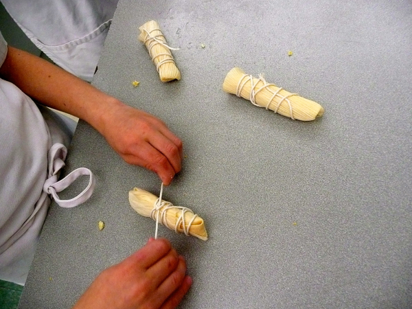 Kids rolling and tying corn husks for tamales by eatlivetravelwrite.com