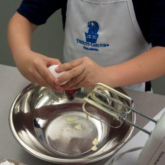 KIds baking cracking eggs to make madeleines by Mardi Michels eatlivetravelwrite.com
