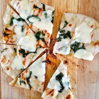 Grilled pizza using Jennifer Perillos dough with mozarella oilve oil and basil Mardi Michels eatlivetravelwrite.com