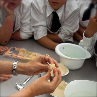 Shayma Saddat showing Les Petits Chefs how to fill and wrap dumplings on eatlivetravelwrite.com