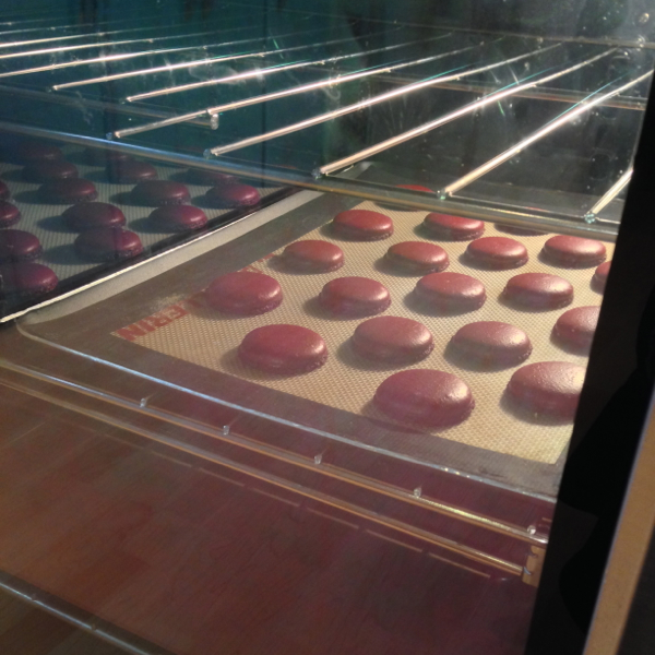 Two trays of macarons side by side in a KitchenAid oven on eatlivetravelwrite.com