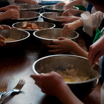 KIds mixing eggs into flour to make pasta dough on eatlivetravelwrite.com