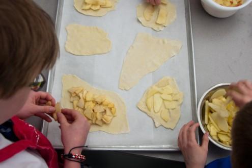 Kids constructing apple tartlets on eatlivetravelwrite.com