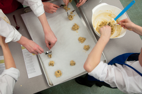 Kids scooping cookies on baking tray on eatlivetravelwrite.com