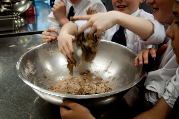 Kids mixing chocolate pasta dough on eatlivetravelwrite.com