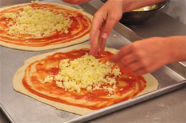 Kids putting Mozarella on pizzas on eatlivetravelwrite.com
