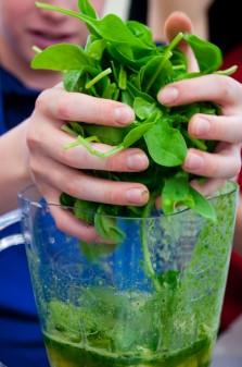 Kids making spinach smoothies on eatlivetravelwrite.com