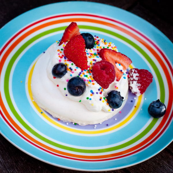 Pavlova topped with fruit and sprinkles on eatlivetravelwrite.com