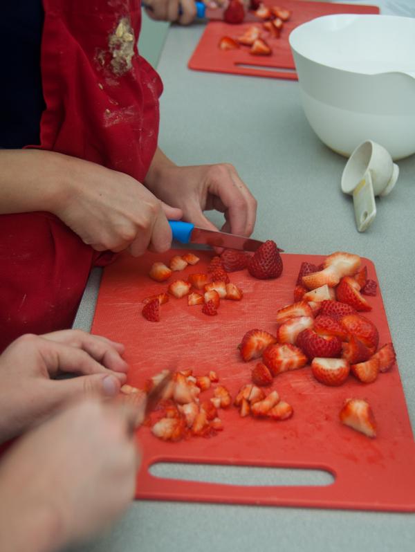 Kids chopping strawberries for jam on eatlivetravelwrite.com