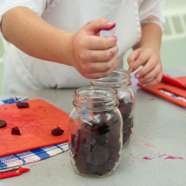 Kids putting beets in mason jars on eatlivetravelwrite.com