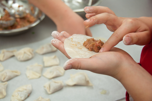 Kids assembling chicken potstickers on eatlivetravelwrite.com
