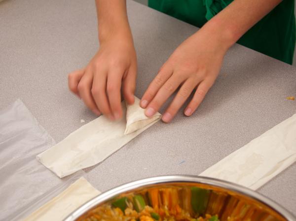 Kids folding sweet potato samosas from The Messy Baker on eatlivetravelwrite.com