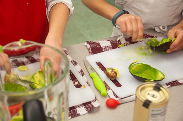 Kids prepping avocado for chocolate pudding on eatlivetravelwrite.com