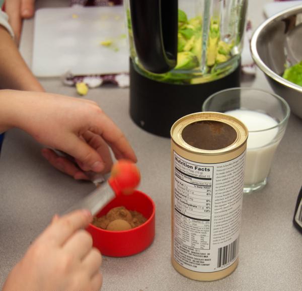 Kids measuring cocoa for chocolate pudding on eatlivetravelwrite.com