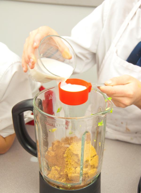 Kids measuring milk for chocolate avocado pudding on eatlivetravelwrite.com
