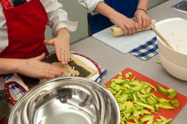 Kids rolling avocado sushi rolls on eatlivetravelwrite.com