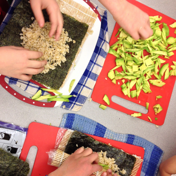 Kids making avocado sushi rolls on eatlivetravelwrite.com