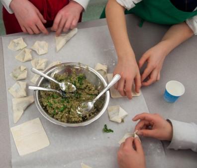 Kids making dumplings for Chinese New Year on eatliveravelwrite.com