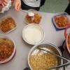Kids putting parmesan cheese on spaghetti bolognese on eatlivetravelwrite.com