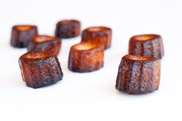 Sideways view of Caneles made with silicone moulds with butter and beeswax on eatlivetravelwrite.com