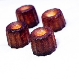 Side view of Caneles made in silicone moulds with butter coating on eatlivetravelwrite.com