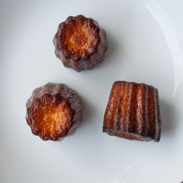 Top view of Caneles made in a Mastrad mold brushed with melted butter on eatlivetravelwrite.com