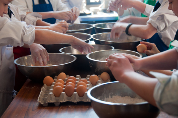 Kids cracking eggs to make fresh pasta on eatlivetravelwrite.com