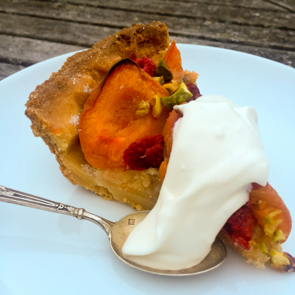 Slice of Dorie Greenspan apricot raspberry tart with cream on eatlivetravelwrite.com