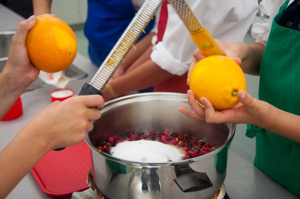 Kids grating orange zest for cranberry sauce on eatlivetravelwrite.com