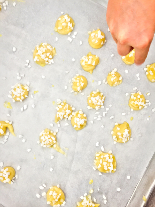 Sprinkling pearl sugar on chouquettes on eatlivetravelwrite.com
