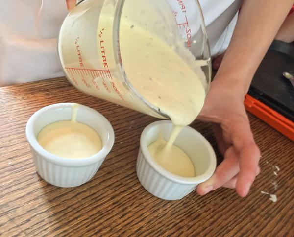 Kids pouring souffle mix into ramekins on eatlivetravelwrite.com
