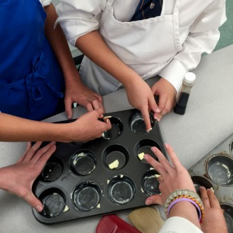 Kids greasing muffin tins on eatlivetravelwrite.com