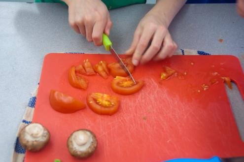 Kids chopping tomatoes for breakfast popovers on eatlivetravelwrite.com