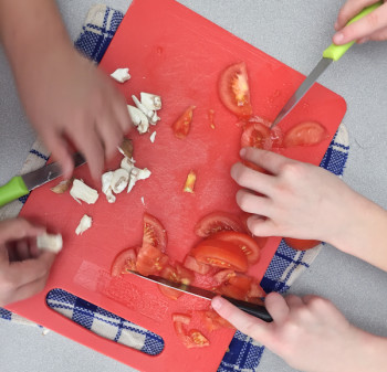 Boys cooking club chopping tomatoes and mushrooms on eatlivetravelwrite.com