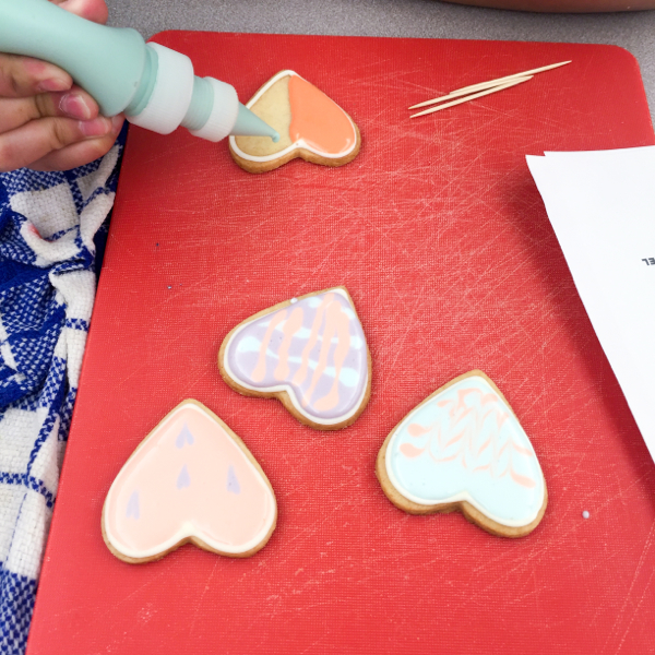 Kids decorating cookies for Valentine's Day on eatlivetravelwrite.com