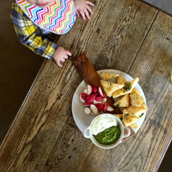 Toddler contemplating Seven Spoons blitzed ricotta with pea pesto on eatlivetravelwrite.com