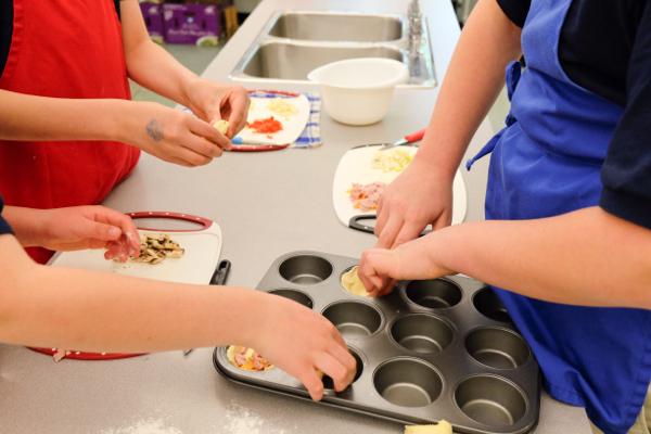 Kids pressing quiche dough into pans on eatlivetravelwrite.com