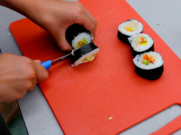 Kids cutting sushi rolls for sushi with John Placko on eatlivetravelwrite.com