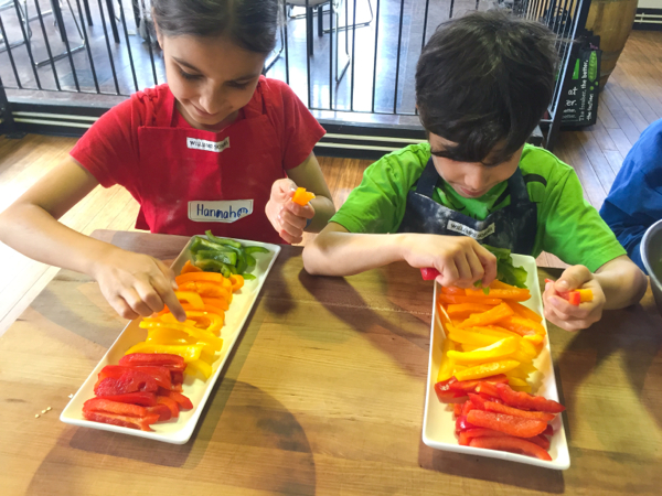Kids arranging peppers for hummus on Food Revolution Day on eatlivetravelwrite.com