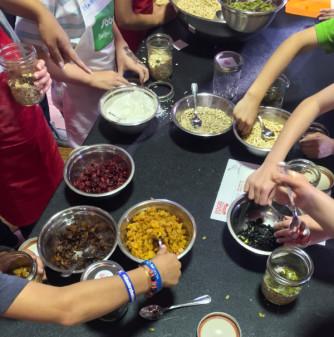 Kids making granola for Food Revolution Day on eatlivetravelwrite.com