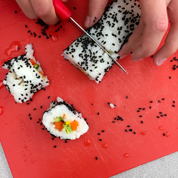 Kids chopping sushi rolls with black sesame seeds Making sushi rolls rolled in wasabi sesame seeds with John Placko on eatlivetravelwrite.com