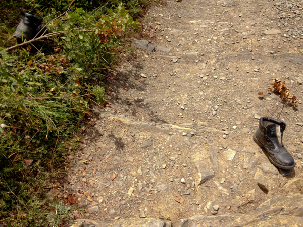 Abandoned shoe on the road to Alto de Erro on Camino de Santiago on eatlivetravelwrite.com