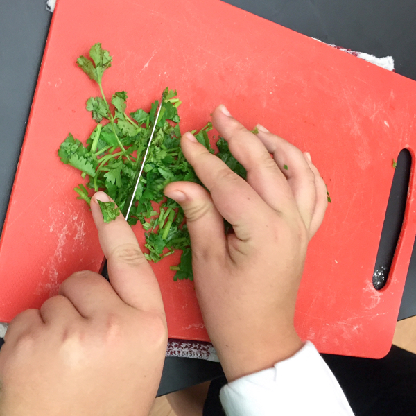 Kids mincing cilantro on eatlivetravelwrite.com